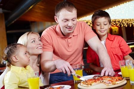 familia comiendo: Retrato de lindos niños y sus padres en la pizzería