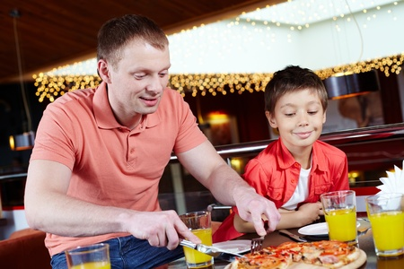 Portrait of handsome man cutting pizza with his son near by in pizzeria Stock Photo - 9725845