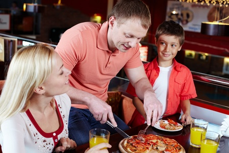 interacting: Portrait of happy family spending time in pizzeria