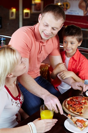 Portrait of happy family having lunch in pizzeria photo