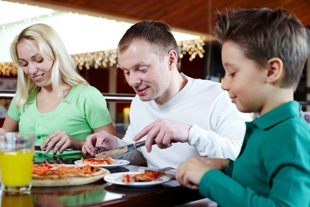 Portrait of family of three having lunch in pizzeria photo