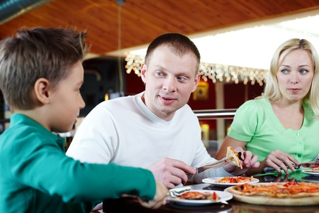 Portrait of family of three eating pizza in cafe Stock Photo - 9725790