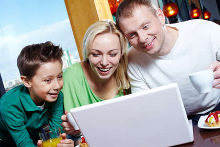 Image of happy family looking at laptop screen in cafe Stock Photo - 9725812