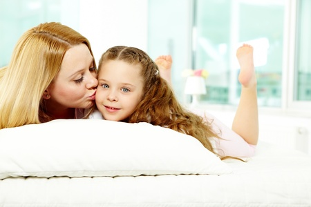 Loving mother kissing her pretty daughter while relaxing on sofa photo