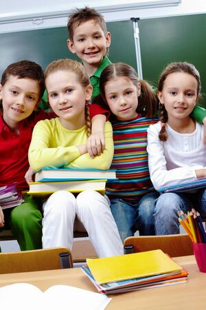 classmate: Portrait of happy children looking at camera in class Stock Photo