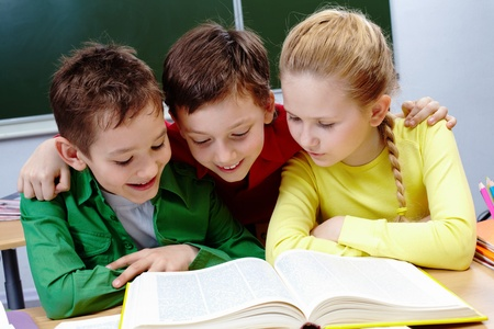 readers: Portrait of two guys and girl reading book in classroom Stock Photo