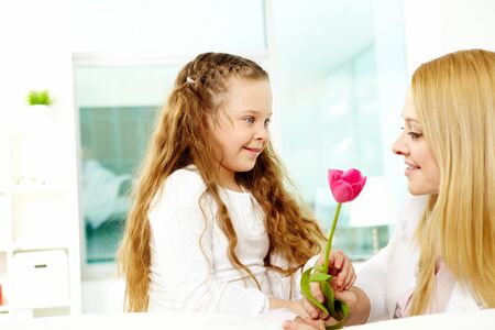 Adorable girl giving beautiful tulip to her mother photo