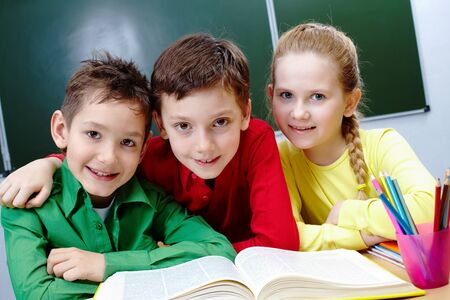 Portrait of two guys and girl sitting in classroom with open book near by Stock Photo - 9725847
