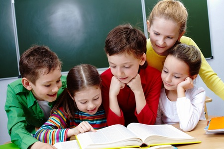 place to learn: Portrait of friendly group reading book in classroom
