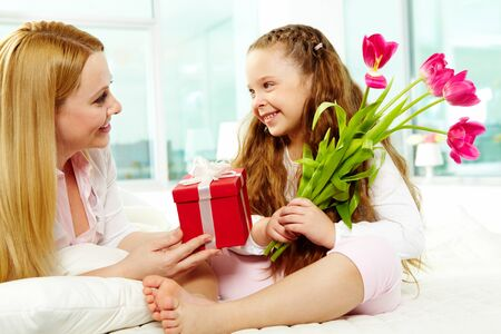 Adorable girl with bunch of beautiful tulips looking at her mother with giftbox photo