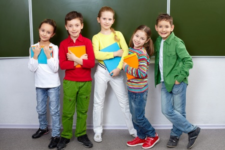 Portrait of five pupils looking at camera in classroom Stock Photo - 9725869