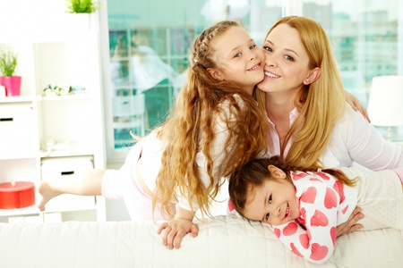 motherhood: Loving mother with her two pretty daughters having rest at home Stock Photo