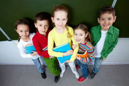Portrait of five pupils looking at camera in classroom photo