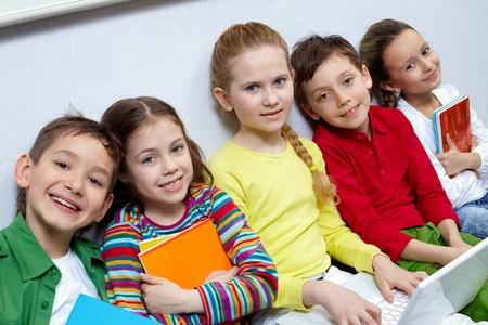 ni�os sentados: Retrato de cinco alumnos mirando la c�mara mientras estaba sentado en el suelo Foto de archivo