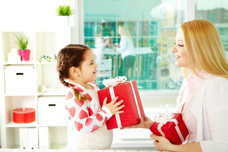giving gift: Adorable girl with big giftbox giving it to her mother