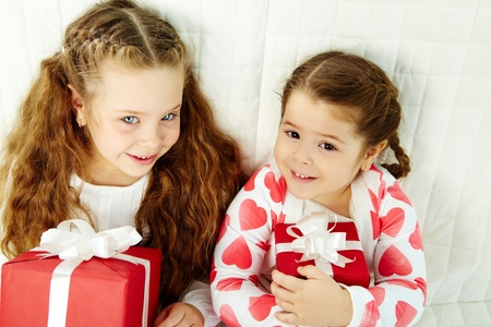 Portrait of happy girls with gifts looking at camera and smiling    photo