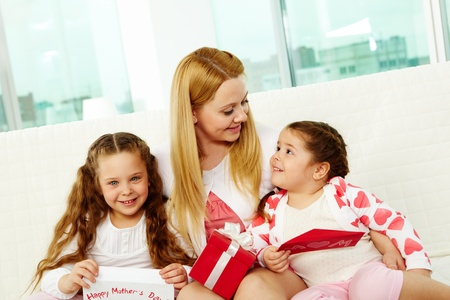 Loving mother with her two pretty daughters interacting at home photo
