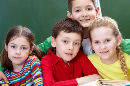 schoolmate: Team of four classmates looking at camera in classroom