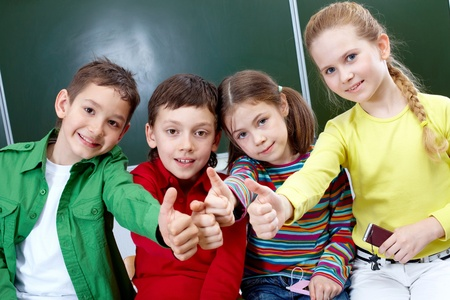 Group of four classmates showing sign of ok photo