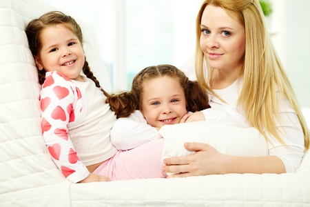 Loving mother with her two pretty daughters having rest at home photo