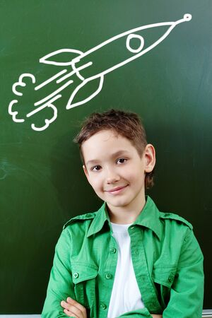 schoolchildren: Portrait of smart lad by the blackboard thinking of airplane and looking at camera Stock Photo
