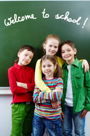 teens school: Group of  happy classmates together by whiteboard with text welcome to school  Stock Photo