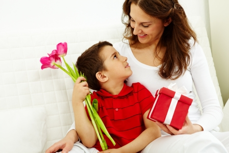 mother and son: Cute lad with bunch of beautiful tulips looking at his mother with giftbox Stock Photo