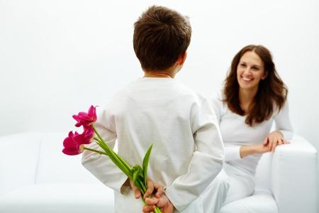 어머니의: 뒤에 아름 다운 튤립의 무리와 함께 젊은이의 후면보기 그의 어머니에 대한 좋은 놀라움을 준비하고