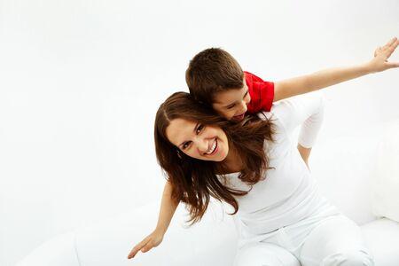 madre e hijo: Ni�o alegre en parte posterior de su madre