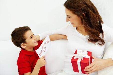 madre e hijo: Chico lindo con la tarjeta de felicitar a buscar a su madre con caja de regalo