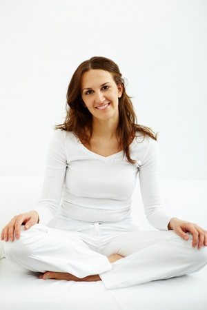 Portrait of happy brunette sitting on white sofa and looking at camera photo