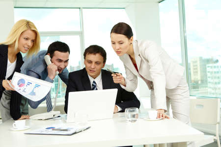 Portrait of several colleagues looking at laptop screen in office Stock Photo - 9725937