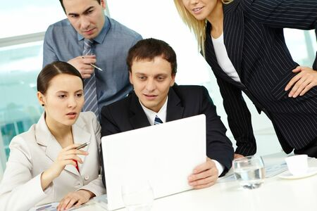 Portrait of several colleagues looking at laptop screen in office Stock Photo - 9725942