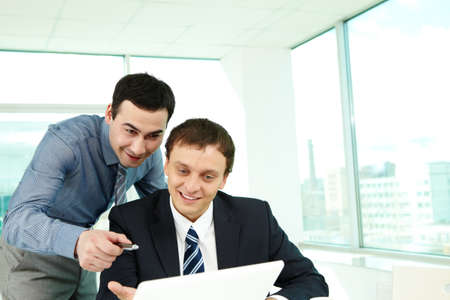 Portrait of confident colleagues looking at laptop screen in office Stock Photo - 9725923