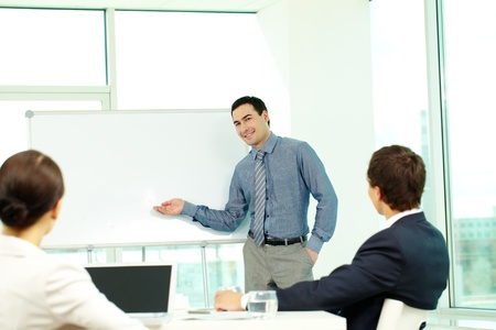 A business man showing something on a whiteboard to his colleagues Stock Photo - 9725902