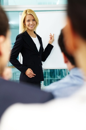 A woman manager pointing at whiteboard with colleagues listening to her photo
