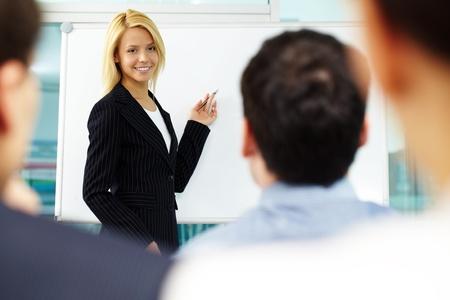 maestra ense�ando: Linda manager apuntando en la pizarra, mientras colegas escuchando a ella Foto de archivo
