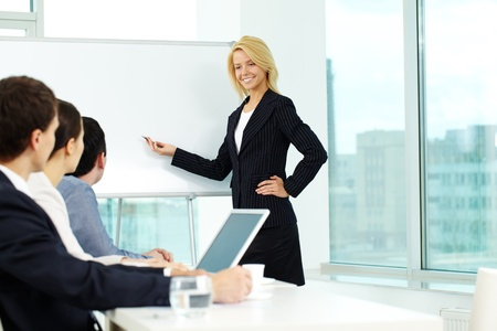 Pretty manager pointing at whiteboard while colleagues listening to her Stock Photo - 9725900