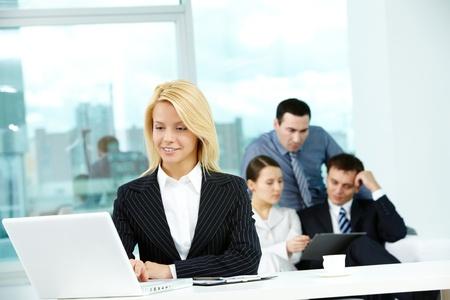 Portrait de jolie secrétaire regardant un écran ordinateur portable dans l'environnement de travail