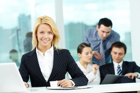 Portrait of pretty secretary looking at camera in working environment photo
