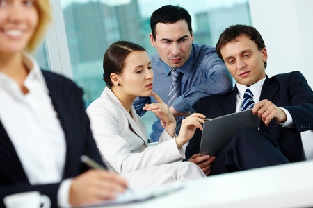 Portrait of several employees discussing plan in office photo