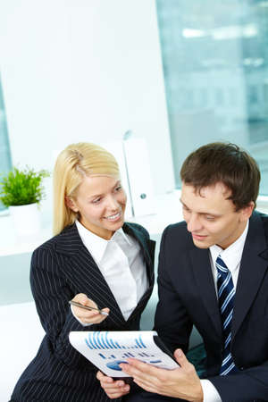 Portrait of confident man looking at document while female explaining it photo