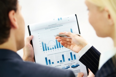 financial strategy: Image of paper being discussed by two business partners