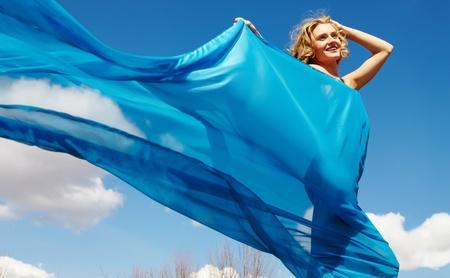 tela seda: Una hermosa ni�a caminando envuelto en cortinas de seda azul Foto de archivo