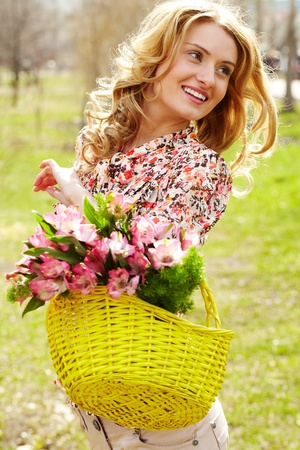 Portrait of young woman holding basket with flowers outside photo