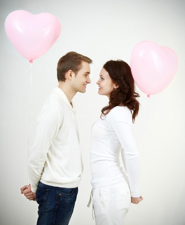 Two beautiful young people with heart-shaped balloons looking at each other Stock Photo - 9726202