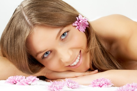 Portrait of beautiful girl with pink daisies looking at camera photo
