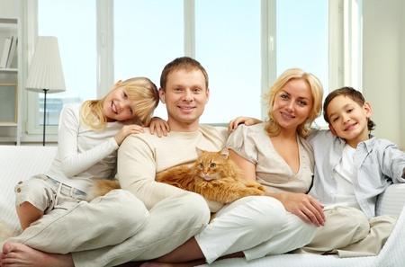 Una familia joven con un hijo y una hija, sentado en el sofá, mirando la cámara y sonriente Foto de archivo