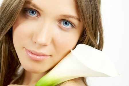 Face of beautiful girl with calla by her face looking at camera photo