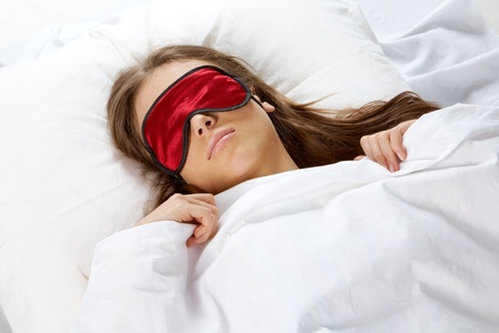 sleeping woman: Portrait of a young girl with eye mask sleeping under blanket